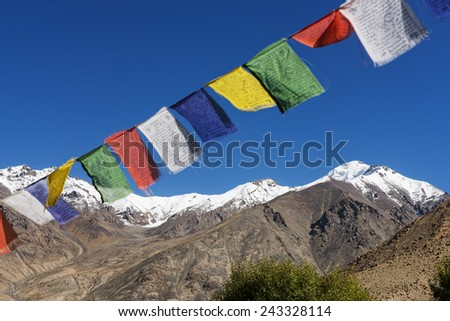 snow mountain range and tibetan prayer flags in the village ,Leh-Nubra Valley Road Ladakh ,India - September 2014