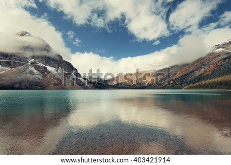 Snow Mountain with fog and lake forest - stock photo