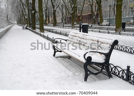 Snow on bench in park of winter. - stock photo