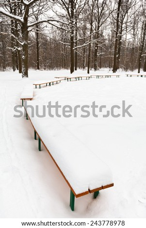 snow on benches in city park in winter - stock photo