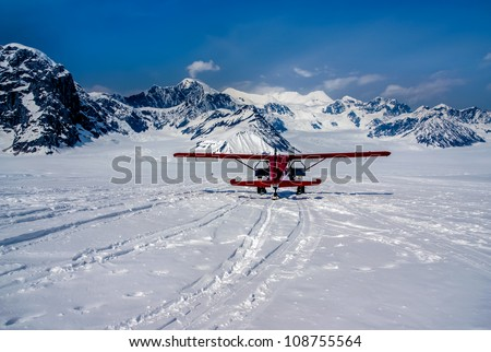 Snow Plane Landing on Ruth Glacier in Denali National Park, Alaska.  The Great Alaskan Wilderness.  A Beautiful Snowscape of Rock, Snow, and Ice. - stock photo