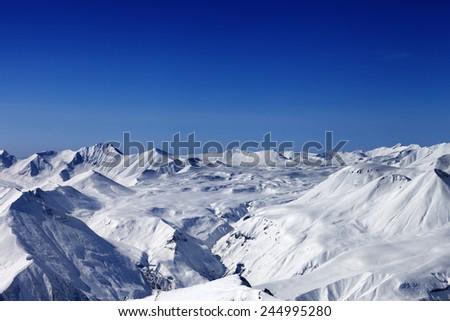 Snow plateau and blue clear sky. Caucasus Mountains, Georgia. View from ski resort Gudauri. - stock photo