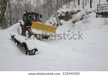 Snow plough clearing path in winter storm - stock photo