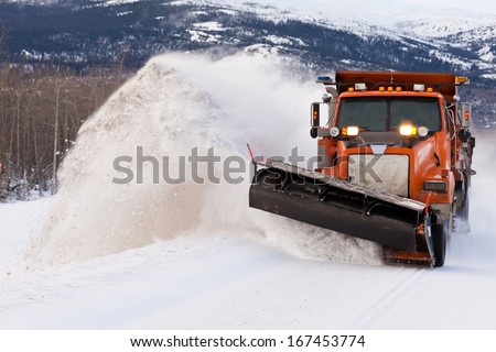 Snow plough truck clearing road after whiteout winter snowstorm blizzard for vehicle access - stock photo