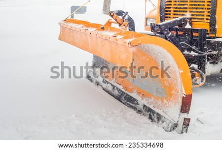 Snow plow doing snow removal after a blizzard in Chicago suberb. - stock photo