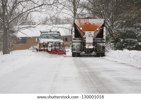 Snow plow removing snow from street. - stock photo