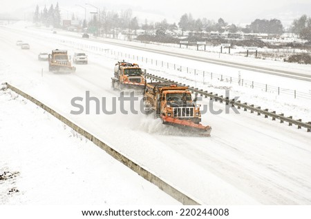 Snow plows clearing the freeway on Interstate 5 during a winter snow and freezing rain storm - stock photo