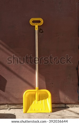 Snow removal. Yellow plastic Shovel, ready for snow removal, outdoors.  - stock photo
