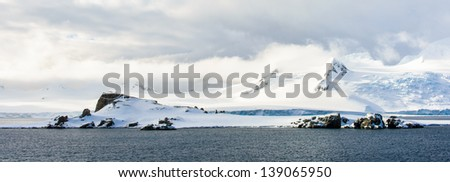 Snow rock on the water under the blue cloudy sky