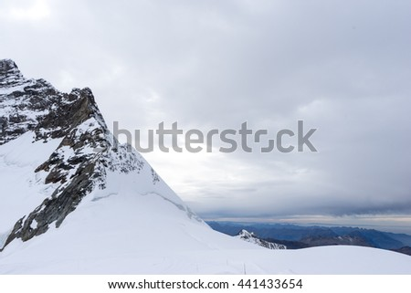 snow scene on alpes mountains in cloud sky