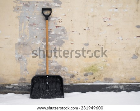 Snow shovel standing against a worn out brick wall - stock photo