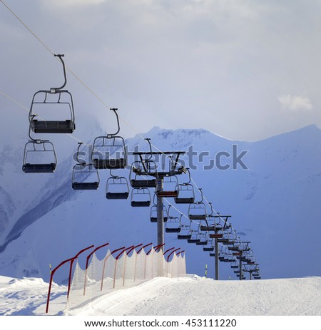 Snow skiing piste and ropeway. Caucasus Mountains. Georgia, ski resort Gudauri in cloudy evening.  - stock photo