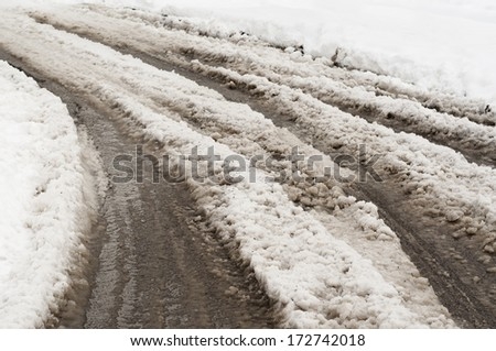 Snow slush on the road. Tire tracks on a snow covered road. - stock photo