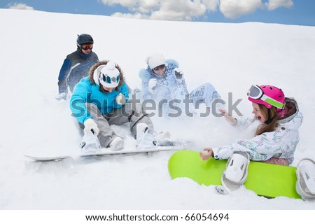 Snow splashes and three young girls sit on the bottom of the mountain