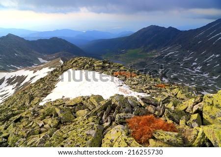 Snow spots on a rock covered ridge under gloomy sky - stock photo