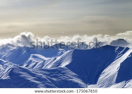 Snow sunlight mountains in evening. Caucasus Mountains, Georgia, view from ski resort Gudauri. - stock photo