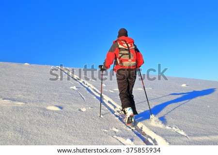 Snow traces and mountaineer woman ascending on touring skis  - stock photo