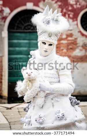 Snow white carnival mask standing in front red wall background with iron green gate holding toy bear, Venice, Italy.