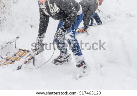 Snow, winter and wooden sledges. Three children sledding, clung to each other