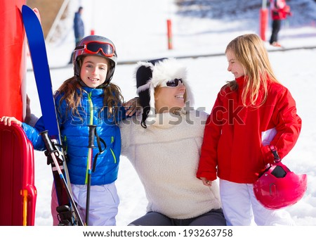 snow winter family in ski track mother and daughters smiling happy with equipment - stock photo