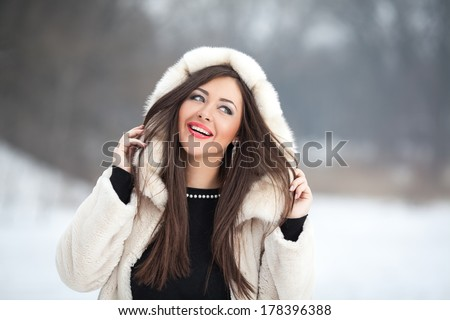 Snow winter woman portrait outdoors on snowy white winter day. - stock photo