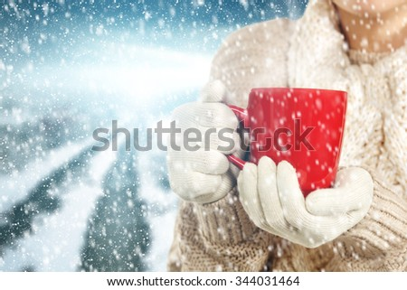snow woman and red mug and road and snowflakes  - stock photo