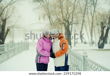 Snowball fight. Winter couple having fun playing in snow outdoors - stock photo