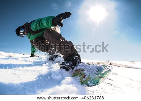 Snowboard freerider in the mountains against sun shine in blue sky. - stock photo