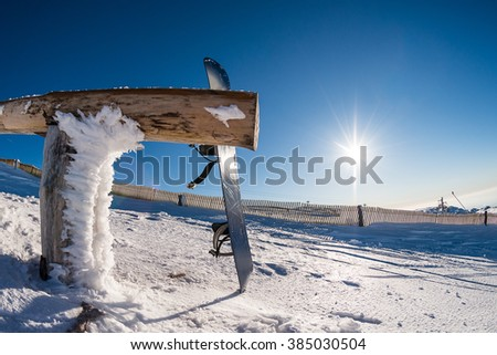 Snowboard leaning on a wood rail on a winter snow covered mountainside and sun shine in blue sky. - stock photo