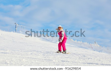 Snowboard rider going down on a resort's hill