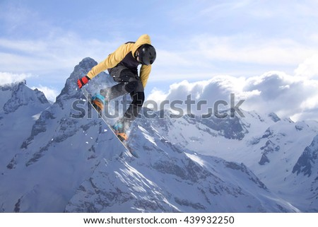 Snowboard rider jumping on mountains. Extreme snowboard freeride sport. - stock photo