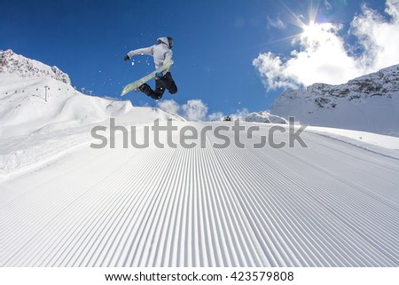 Snowboard rider jumping on winter mountains. Extreme snowboard freeride sport.