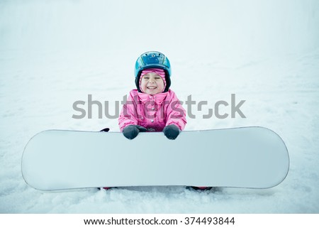 Snowboard Winter Sport. Little kid girl playing with snow wearing warm winter clothes. Winter background - stock photo
