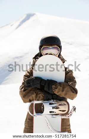 snowboarder and snowboard, portrait on a background of mountains