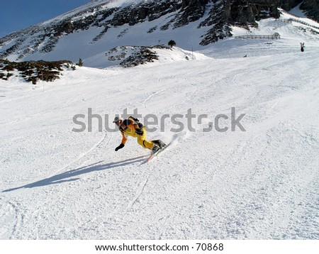 Snowboarder  carving a nice trail in the snow - stock photo