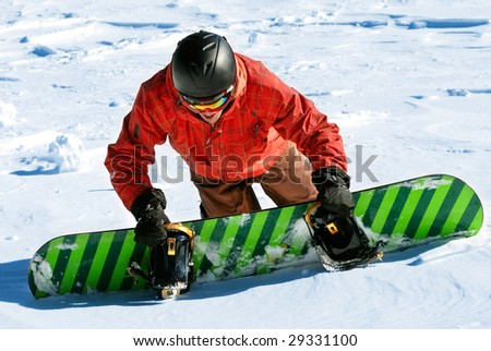 Snowboarder climbing wild snow slope