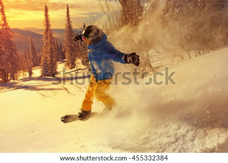 Snowboarder doing a toe side carve with deep blue sky in background. - stock photo