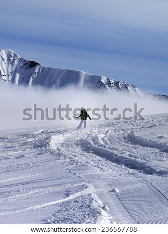 Snowboarder downhill on off-piste slope in sunny day. Ski resort Gudauri. Caucasus Mountains, Georgia. - stock photo