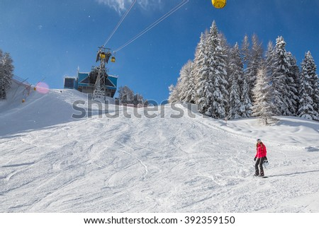 Snowboarder girl in Alps snowing under the ski lifts in Alps - stock photo