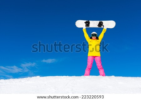 snowboarder girl raised arms standing hold snowboard, snow mountain slope copy space blue sky