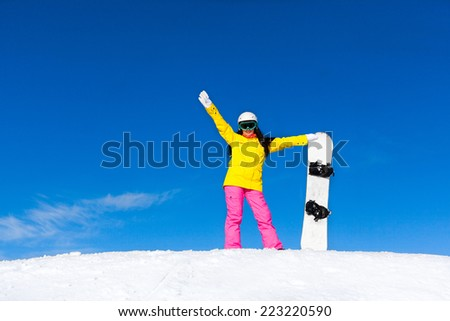 snowboarder girl raised hand up standing hold snowboard, snow mountain slope copy space blue sky