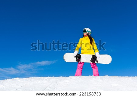 snowboarder girl standing hold snowboard, snow mountain slope copy space blue sky
