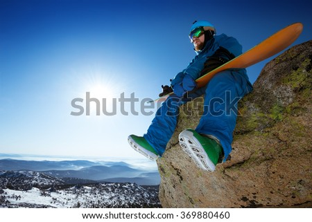 Snowboarder holds snowboard in hands sits on big rock on mountains backdrop. Space for text. Sheregesh resort, Siberia, Russia - stock photo