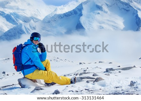 Snowboarder in helmet and goggles, with backpack sitting on the mountain rock  - stock photo