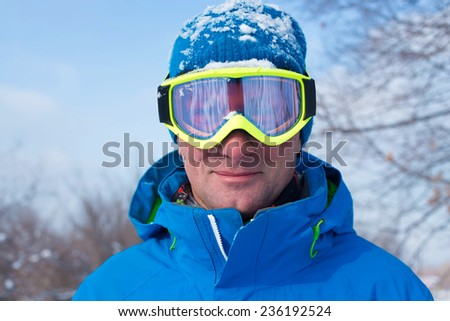 Snowboarder in mask looking into the camera - stock photo
