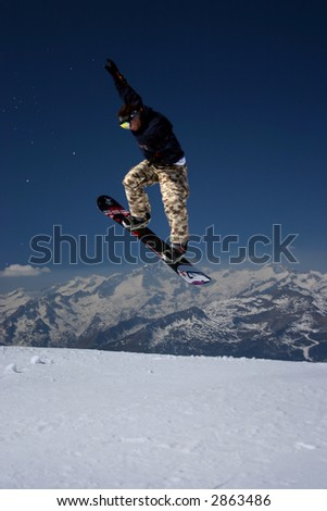 Snowboarder in moro desert pants jumping high - winter mountain action scene