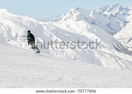 Snowboarder in winter snow mountain landscape with blue cloudy sky. Alps. France. - stock photo