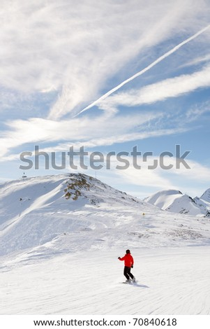 Snowboarder in winter snow mountain landscape with blue cloudy sky. Alps. France.