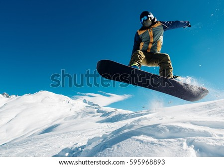 snowboarder is jumping with snowboard from snowhill very high
