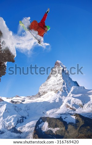 Snowboarder jumping against Matterhorn in Switzerland - stock photo